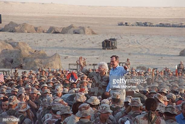 President George HW Bush waves with wife Barbara as they are surrounded by US troops at a US base in Saudi Arabia Thanksgiving Day 1990