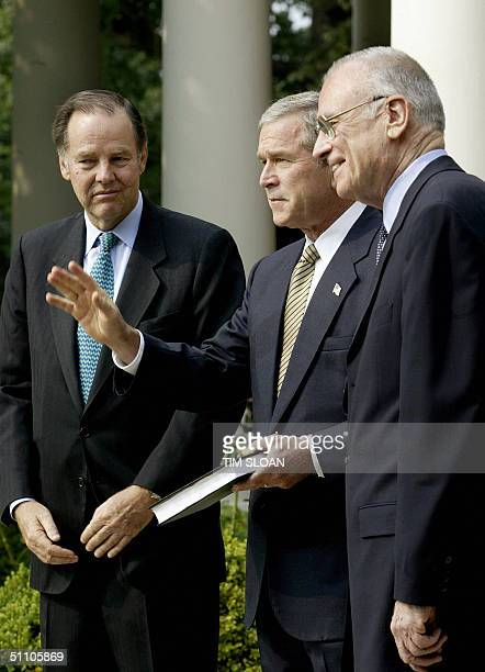 President George W Bush accepts a copy of the 9/11 Commission Report from commission chairman Thomas Kean and vice chairman Lee Hamilton 22 July 2004...