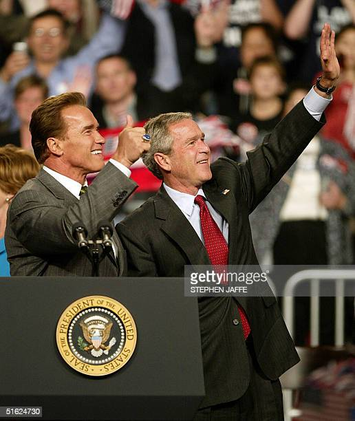 President George W Bush along with California Governor Arnold Schwarzenegger acknowledge the crowd during a campaign rally at Nationwide Arena 29...