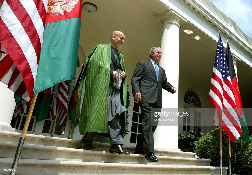 U.S. President George W. Bush (R) and Afghan President Hamid Karzai walk into the Rose Garden for a press conference at the White House June 15, 2004 in Washington DC. The two leaders met to discuss the war on terrorism.