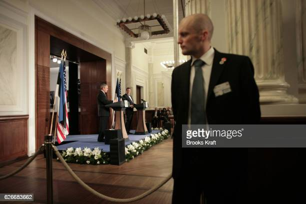 US President George W Bush and Estonian President Toomas Hendrik Ilves speak to reporters as a Estonian security agent watches at the Independence...