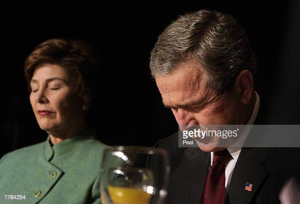 S President George W Bush and first lady Laura Bush bow their heads in prayer as they attend the National Prayer Breakfast February 6 2003 in...