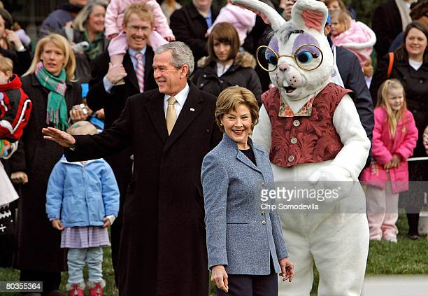 S President George W Bush and first lady Laura Bush stand with a person dressed as the Easter Bunny while welcoming guests to the annual Easter Egg...