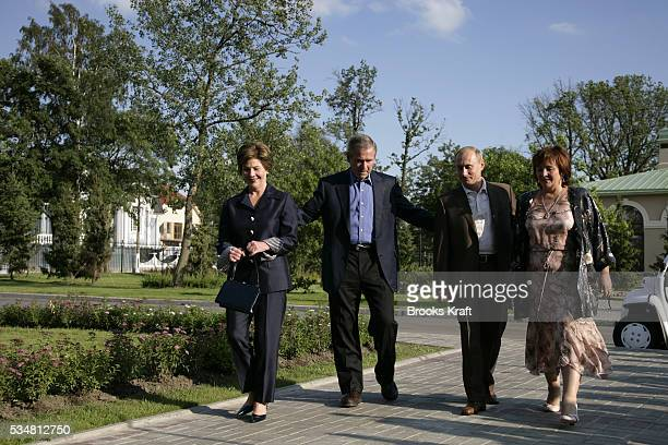 President George W. Bush and first lady Laura Bush walk to a social dinner with Russian President Vladimir Putin and his wife Lyudmila on the grounds...