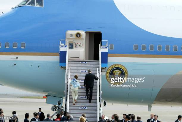 President George W. Bush and first lady Laura Bush walk up the steps to Airforce One as they depart from Tokyo International Airport October 18, 2003...