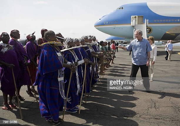 US President George W Bush and First Lady Laura Bush watch Maasai dancers greeting them February 18 2008 upon arrival at Kilimanjaro International...