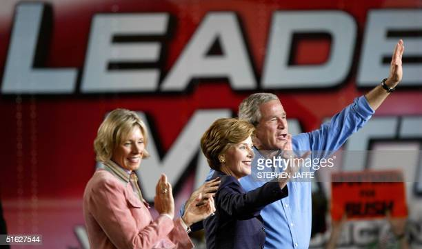 President George W Bush and First Lady Laura Bush wave after they were introduced by the Chair of the Michigan Republican Party Betsy DeVos 30...