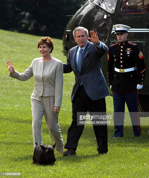 US President George W Bush and First Lady Laura Bush wave as they return to the White House in Washington DC 12 October 2003 after a stay at Camp...