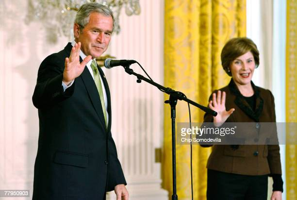 President George W Bush and first lady Laura Bush wave goodbye after delivering remarks on National Adoption Day in the East Room of the White House...