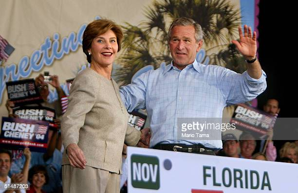 S President George W Bush and first lady Laura Bush wave to supporters at a Florida Victory 2004 rally at Sound Advice Amphitheatre October 16 2004...
