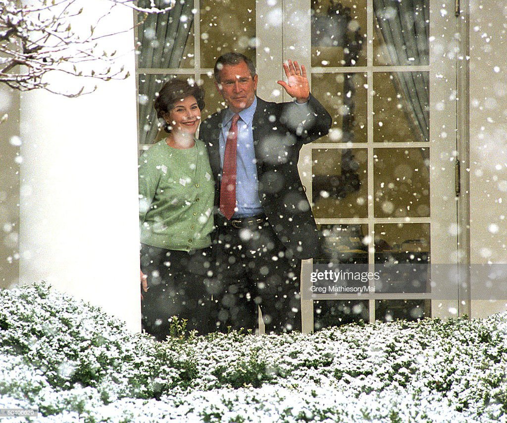 President George W. Bush (R) and First Lady Laura (L) waving on the colonnade outside the Oval Office watching snow fall on the Rose Garden.