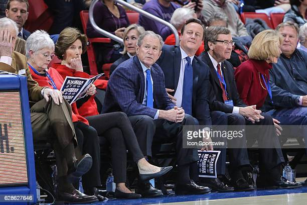 President George W Bush and former UK Prime Minister David Cameron sit courtside during the NCAA men's basketball game between SMU and TCU on...