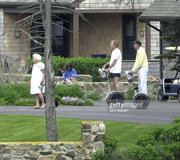 President George W. Bush and former U.S. President George Bush ride on Segway scooters as former first lady Barbara Bush walks at their family home...