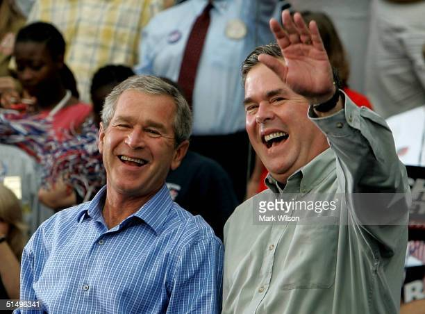 S President George W Bush and his brother Florida Governor Jeb Bush smile while greeting supporters during a campaign rally at Progress Energy Park...