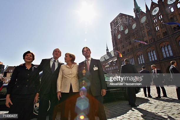 President George W Bush and his wife Laura Bush are greeted by German Chancellor Angela Merkel and her husband Joachim Sauer R upon their arrival on...