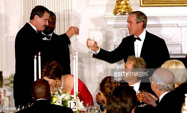 President George W. Bush and Mexican President Vicente Fox raise their glasses in a toast September 5, 2001 at a state dinner for Fox at the White...