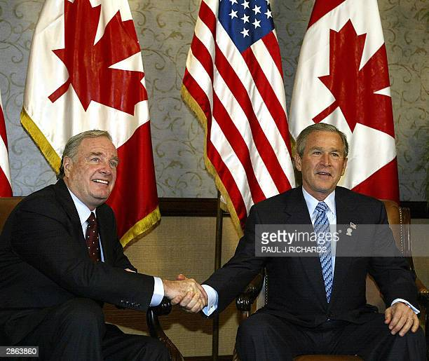 President George W. Bush and new Canadian Prime Minister Paul Martin shake hands during a bilateral breakfast meeting during the Summit of the...