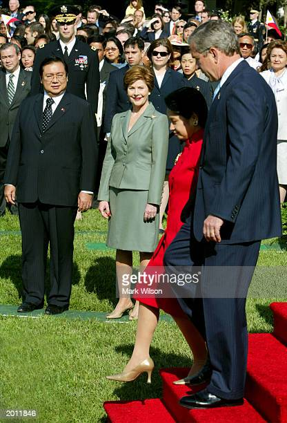 President George W. Bush and Philippines President Gloria Macapagal Arroyo walk past Arroyo's husband, Jose Miguel T. Arroyo , and first lady Laura...