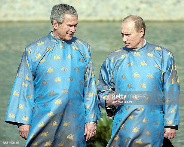 US President George W Bush and Russian President Vladimir Putin both wearing a Vietnamese 'ao dai' silk tunic speak as they take part in the official...