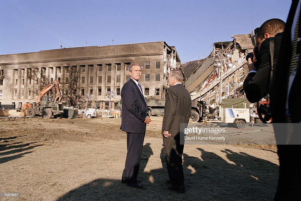 President George W. Bush and Secretary of Defense Donald Rumsfeld survey the damage at the Pentagon building September 12, 2001 in Arlington, VA a day after the September 11, 2001 terrorist attacks in Washington, D.C and New York.