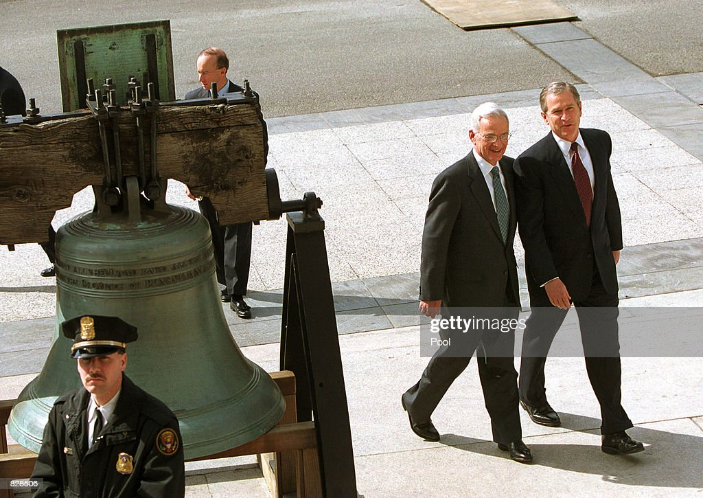 U.S. President George W. Bush and Secretary of Treasury Paul O''Neill walk by a replica of the Liberty Bell March 7, 2001 on their way to the Treasury Building in Washington, DC. The president and secretary were discussing tax relief and tax reform.