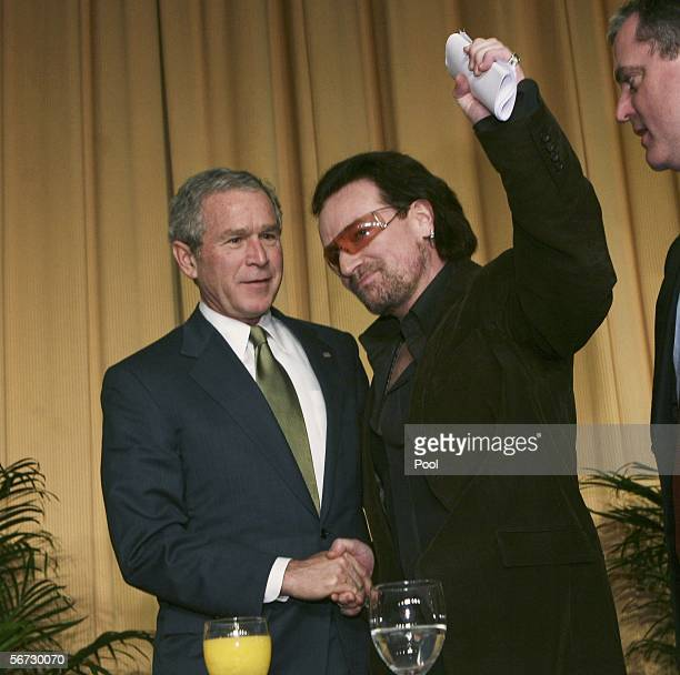 US President George W Bush and singer of the group U2 Bono shake hands after Bono spoke at the National Prayer Breakfast February 2 2006 in...
