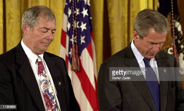 S President George W Bush and Steve Versace bow their heads in prayer in the East Room of the White House July 8 2002 in Washington DC Versace...