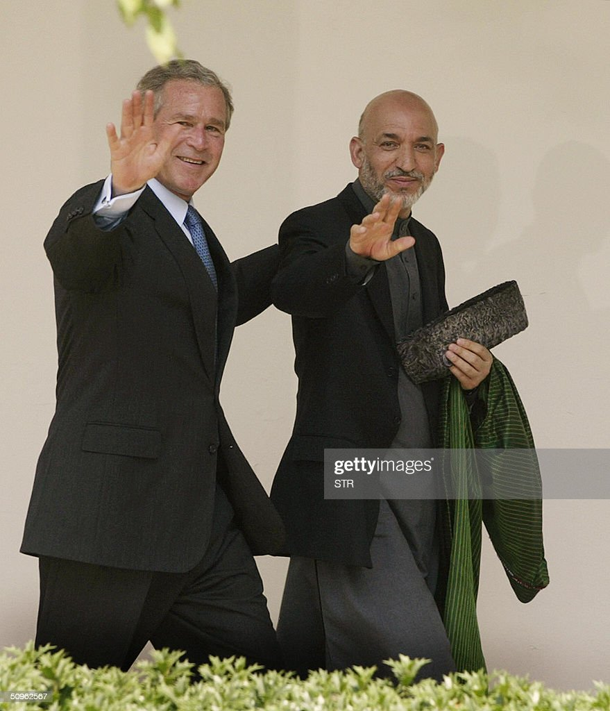 US President George W. Bush (L) and the President of Afghanistan Hamid Karzai wave to reporters in the Rose Garden at the White House in Washington, DC 15 June 2004. The US and Afghanistan will pursue a bilateral trade deal in a bid to boost the country's post-Taliban economic recovery, Bush said Tuesday after meetings with Karzai. 'A bilateral trade agreement will add new fuel to the economic revival' in Afghanistan since the ouster of the Taliban by US-led forces, Bush said. AFP PHOTO/Brendan SMIALOWSKI