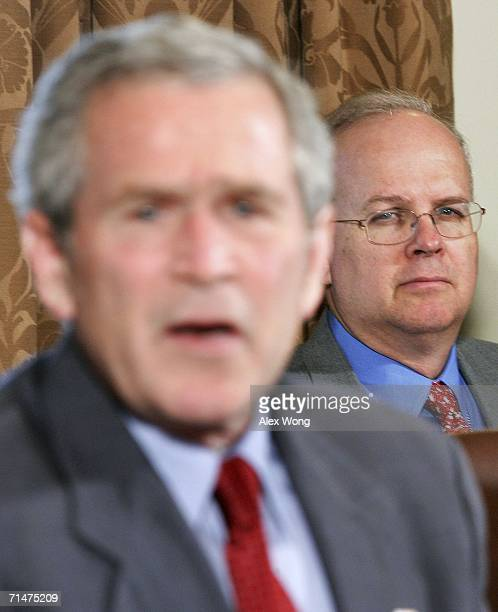 US President George W Bush answers questions from the media as White House advisor Karl Rove looks on at the end of a meeting with congressional...