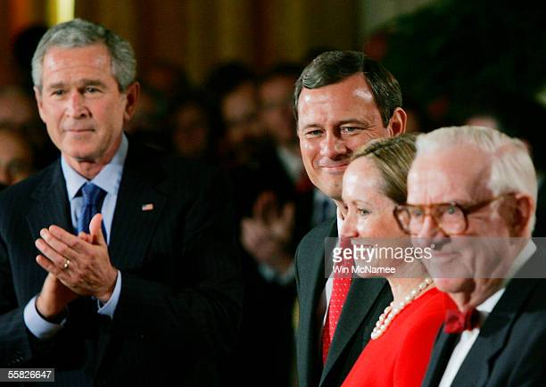 President George W. Bush applauds as John Roberts is welcomed to the East Room prior to being sworn in as Chief Justice of the United States Supreme...