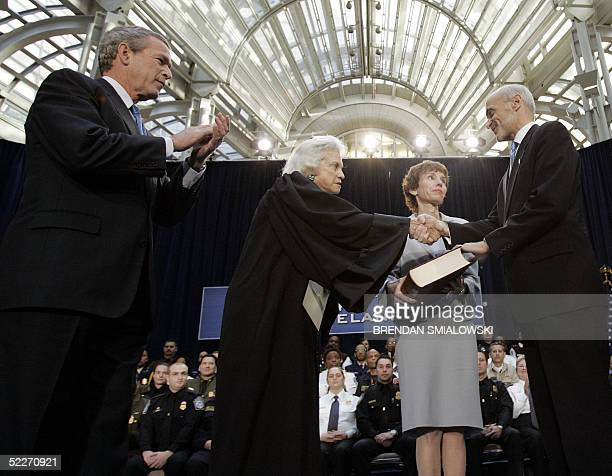 President George W Bush applauds while Michael Chertoff shakes hands with Supreme Court Justice Sandra Day O'Connor while his wife Meryl looks on...