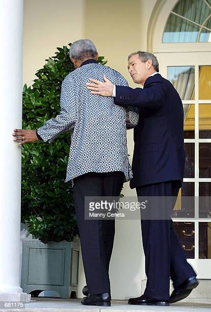 President George W. Bush assists Former South African President Nelson Mandela after delivering their message of condolences to the relatives of the...