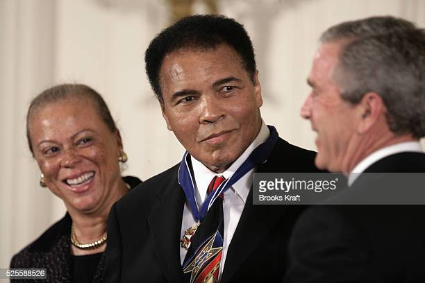 US President George W Bush awards boxing legend Muhammad Ali with the Presidential Medal of Freedom as Ali's wife Lonnie watches during a ceremony in...