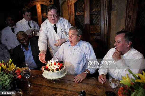 US President George W Bush blows out the candles on his 60th birthday cake during a private dinner party at a restaurant in Chicago July 6 2006...