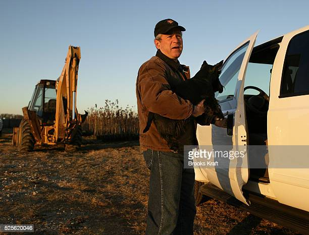US President George W Bush carries his dog Barney as he prepares to drive to his daily intellegence briefing on the Bush Ranch in Crawford Texas