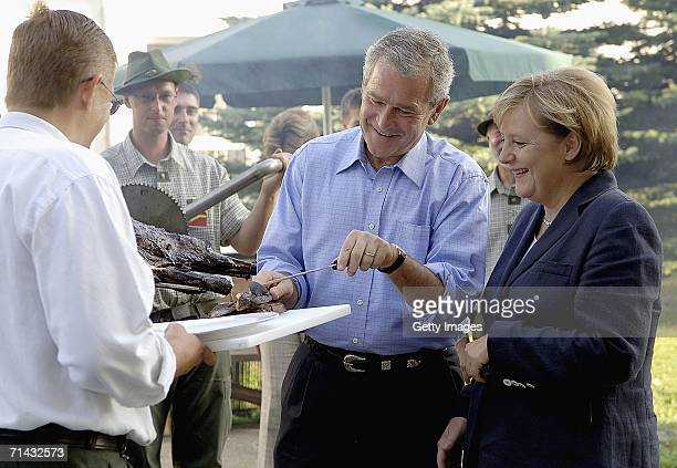 President George W. Bush carves a grilled wild boar during a barbecue with German Chancellor Angela Merkel on July 13, 2006 in Trinwillershagen near...