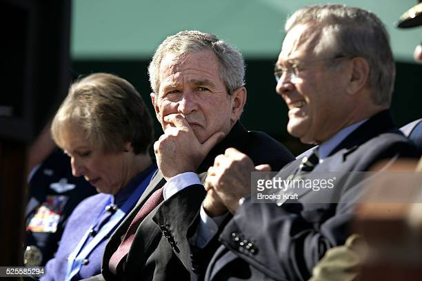 President George W. Bush, center, and Secretary of Defense Donald Rumsfeld, right, watch a flyover during an Armed Forces farewell tribute in honor...