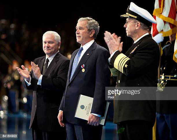 US President George W Bush center is applauded by Robert Gates Secretary of Defense left and Admiral Michael Mullens Chairman of the Joint Chiefs of...