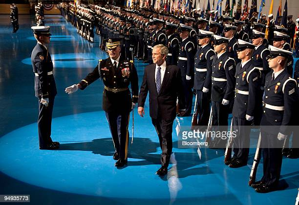 S President George W Bush center right turns after reviewing the troops during the Military Appreciation Parade at Fort Myer in Arlington Virginia US...