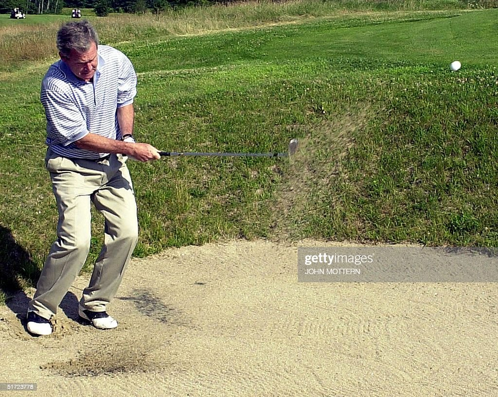 US President George W. Bush chips out of a sand tr : News Photo
