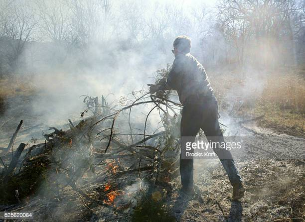 US President George W Bush clears and burns cedar underbrush on the Bush Ranch in Crawford Texas In the dry climate the cedar absorbs a significant...