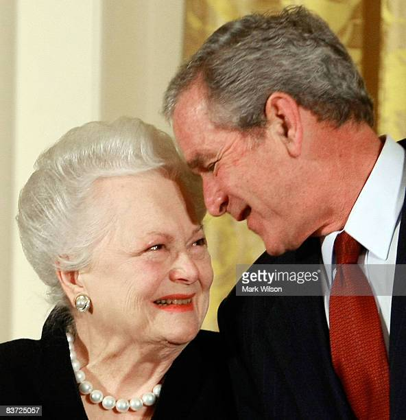 S President George W Bush congratulates actress Olivia de Havilland before presenting her with the 2008 National Medals of Arts award during an event...