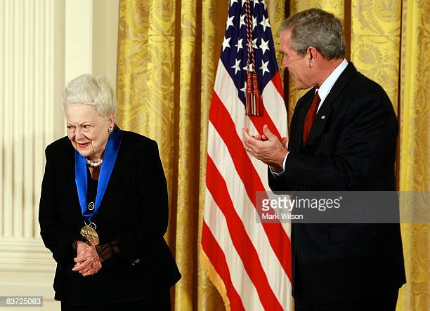 S President George W Bush congratulates actress Olivia de Havilland after presenting her with the 2008 National Medals of Arts award during an event...
