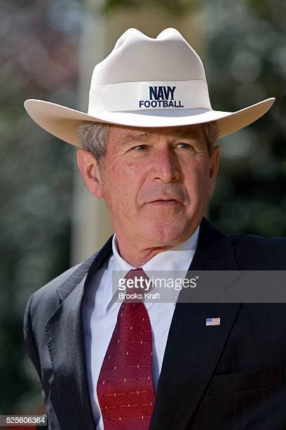 President George W Bush dons a stetson cowboy hat given to him by members of the US Naval Academy football team winners of the CommanderinChief's...