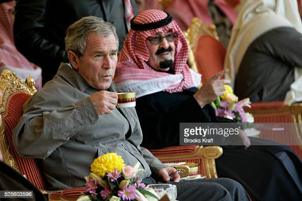 US President George W Bush drinks tea as he and Saudi King Abdullah watch as the King's horses are paraded during his visit to Al Janadriyah Farm in...