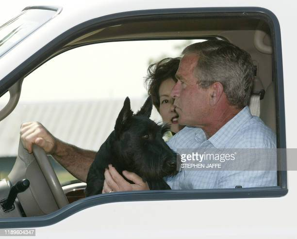 US President George W Bush drives off in his pickup truck with his dog Barney and Secretary of Labor Elaine Chao after he spoke to the media with his...
