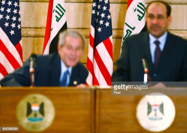 S President George W Bush ducks as an Iraqi man throws his shoes at the President during a joint press conference with Iraq's Prime Minister Nuri...