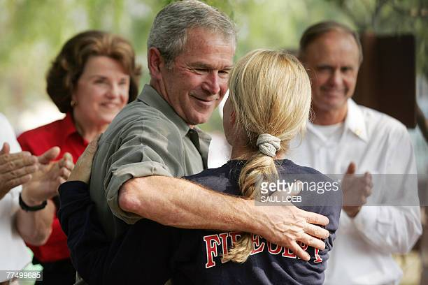 US President George W Bush embraces a first responder prior to having lunch with them while they fight the Southern California wildfires in Escondido...