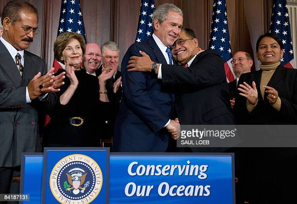 US President George W Bush embraces Governor Benigno Fitial of Northern Mariana Islands after signing a proclamation announcing the creation of the...