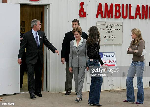 S President George W Bush flanked by his wife Laura and daughters Barbara and Jenna walks out of the Crawford Fire Department after casting his...
